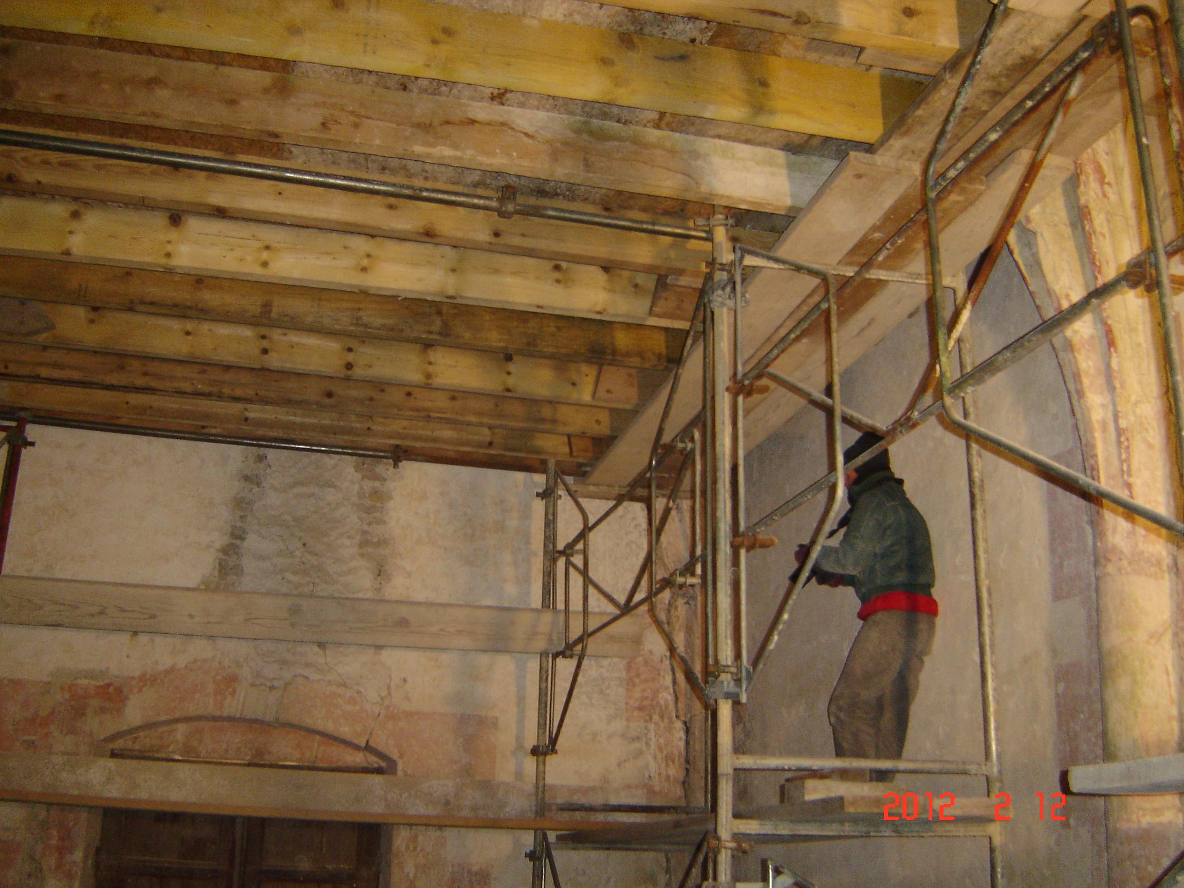 une restauratrice travaille sur la préparation des murs